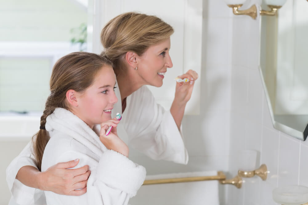 happy-mother-daughter-brushing-teeth-together